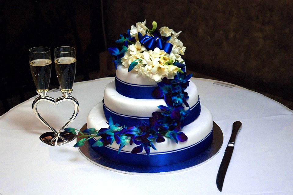 White wedding cake with blue accents and flowers