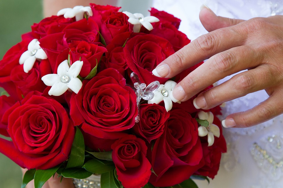 Bouquet of red roses accented with bejeweled white flowers