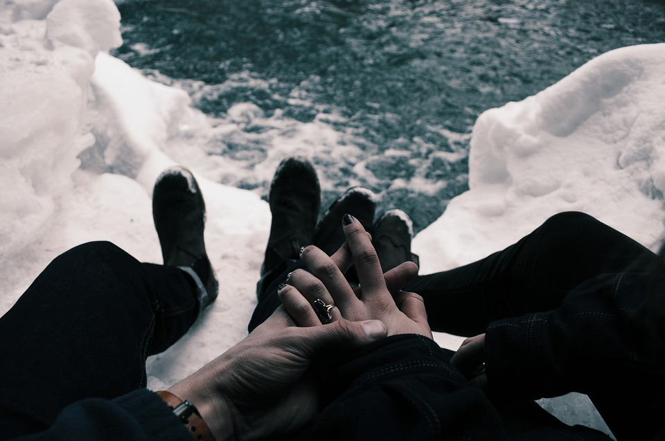 Couple holding hands with wedding rings, sitting on glacier