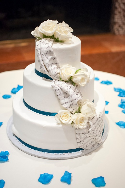 White wedding cake with musical note ribbon and white flowers