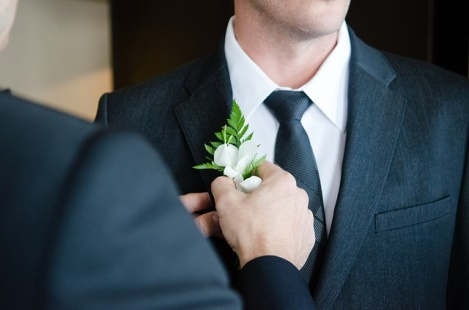 Groom adjusting his boutonniere