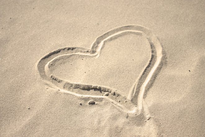 Heart drawn in the sand at the beach
