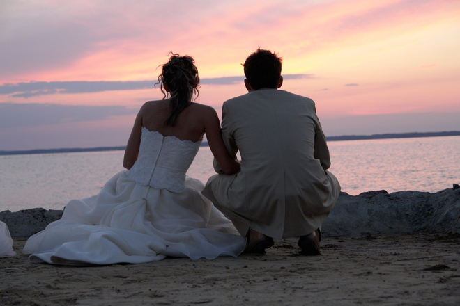 Wedding couple sitting on beach looking at the sunset