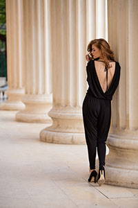 Beautiful young woman wearing backless jumpsuit. Urban fashion