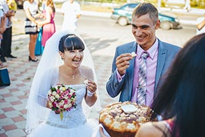 Groom holding slice of traditional wedding round loaf and bride salt it