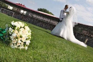Bride and groom embracing with flowers at the forefront