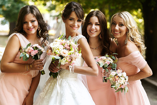 Bride with bridesmaids on the park on the wedding day