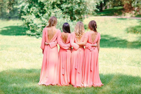 Bridesmaids on the lawn. Bridesmaids in pink dresses.