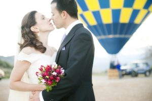 Couple just married embracing before hot air balloon