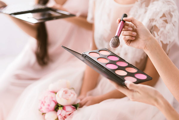 Young bridesmaid holding the palette of blusher