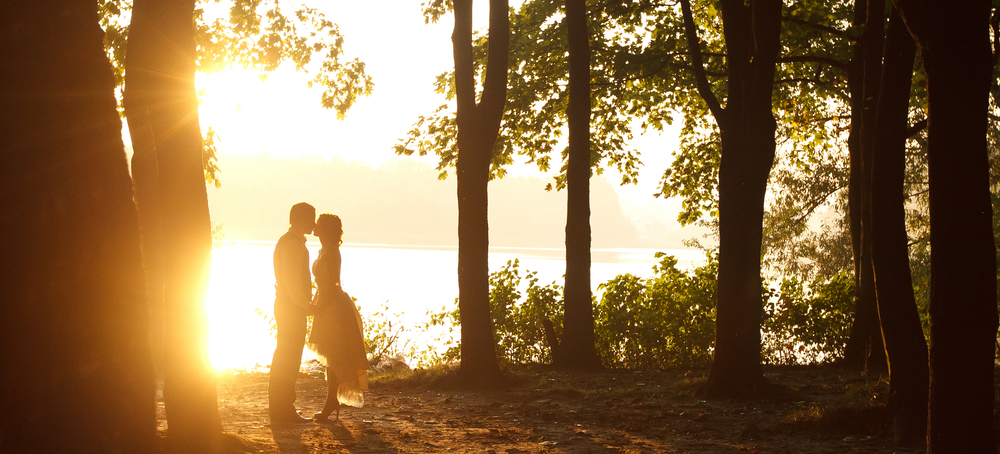 silhouette of married couple kissing in forest