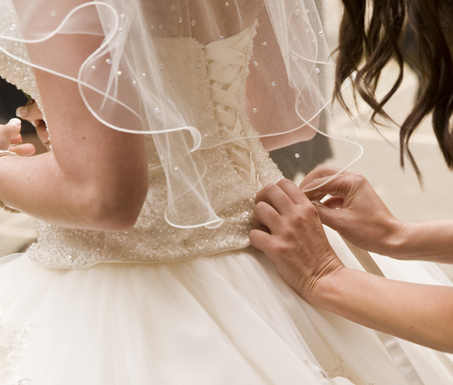 corset of wedding dress being laced by woman