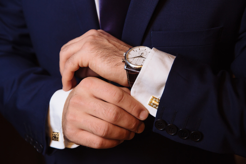 man adjusting cuff links wearing watch