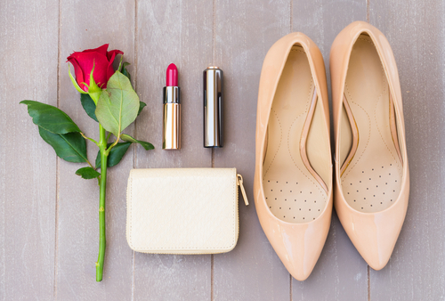 nude colored heels with wallet and flower