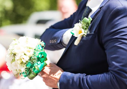 wedding bouquet in hands of groom