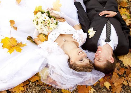 Bride and groom on fall leaves