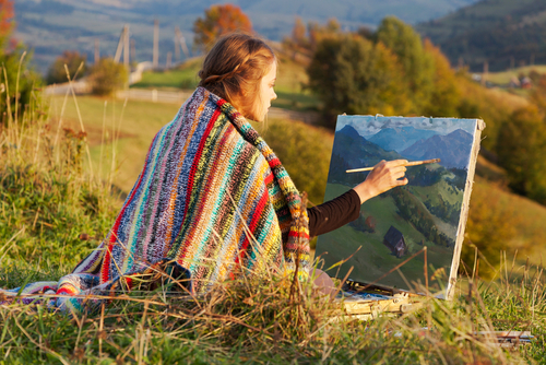 woman outdoors painting landscape