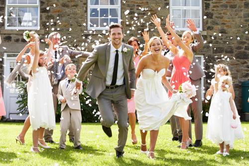 guests throwing confetti bride groom
