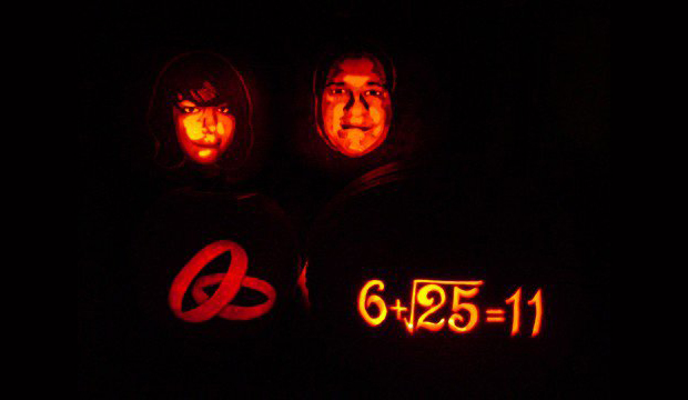 Amy and Tim's save the date featured carved pumpkins of their faces and wedding date in the form of a math equation.